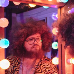 [Image Description: Kyron is wearing 70's style glasses and a shirt with a psychedelic print, he has a large voluminous afro of curly hair and a large beard. He is looking at a reflection of himself backstage, in a mirror framed by lightbulbs, bathed in orange, purple and pink light].